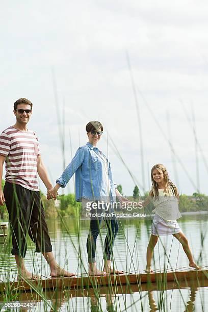 Family holding hands on dock, portrait
