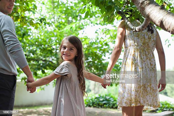 family holding hands together outdoors - looking over shoulder stock pictures, royalty-free photos & images