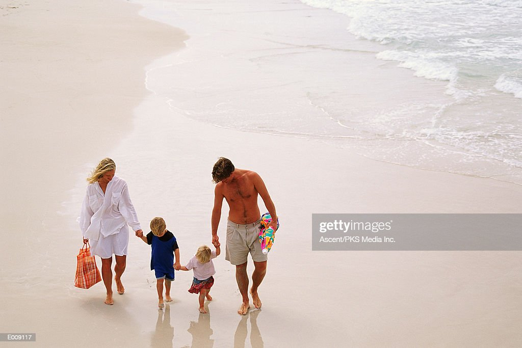 Family holding hands, walking along beach : Stock-Foto