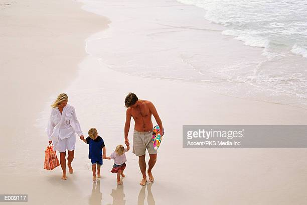 family holding hands, walking along beach - generic location stock pictures, royalty-free photos & images