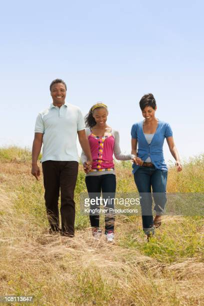 Family holding hands walking down hill