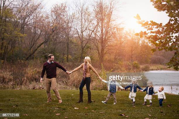 family, holding hands, walking forward in line - volgen activiteit stockfoto's en -beelden
