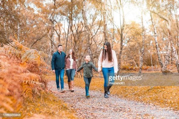family holding hands walking in park during autumn - father stock pictures, royalty-free photos & images