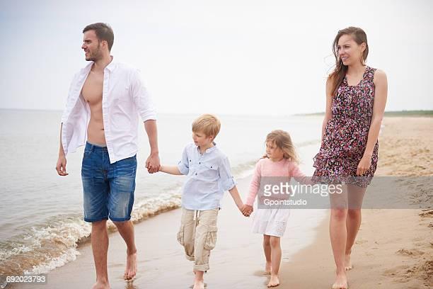 family holding hands walking on beach - helemaal losgeknoopt stockfoto's en -beelden