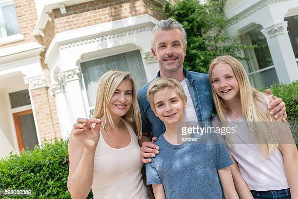 Family holding keys to their new house