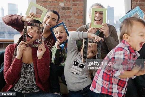Family holding picture frames over faces