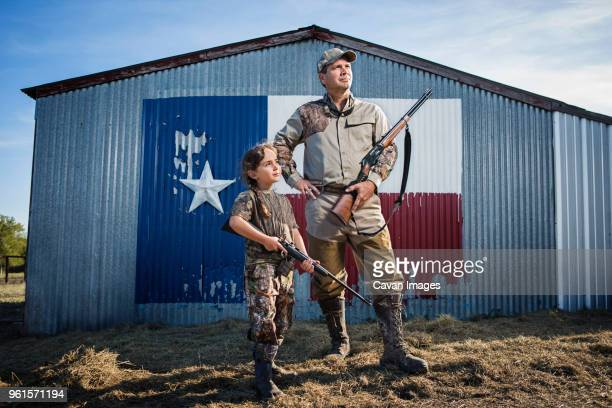 Family holding rifle while standing on field against Texas flag