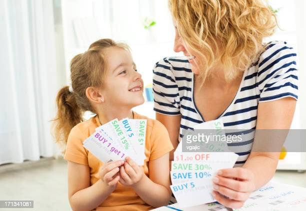 family holding shopping coupons. - coupon stock photos and pictures