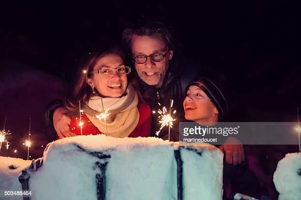 family holding sparkling bengal fire outdoors at night in winter. - bengal new year stock photos and pictures