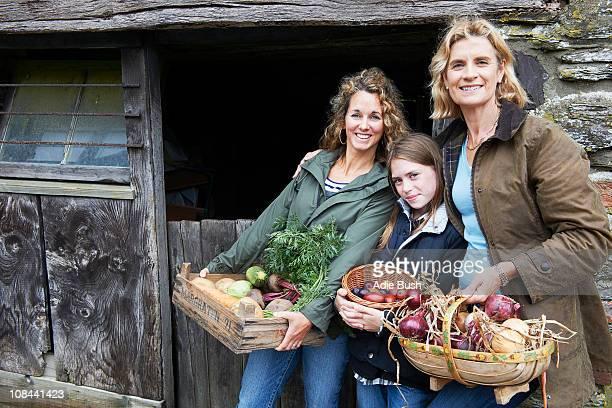 Family holding vegetables