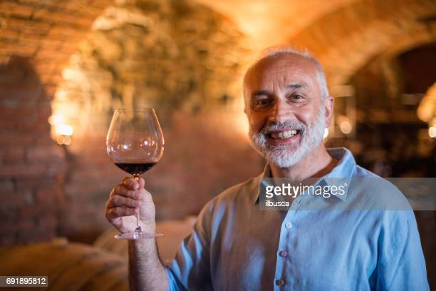 Family holidays in Langhe region, Piedmont, Italy: Man choosing and tasting wine