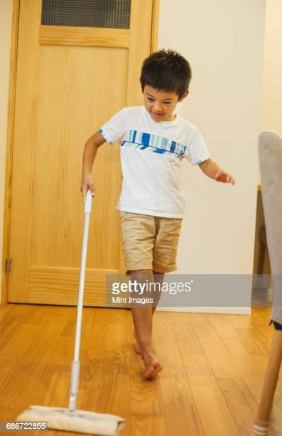 Family home. A boy with a mop cleaning a wooden floor.