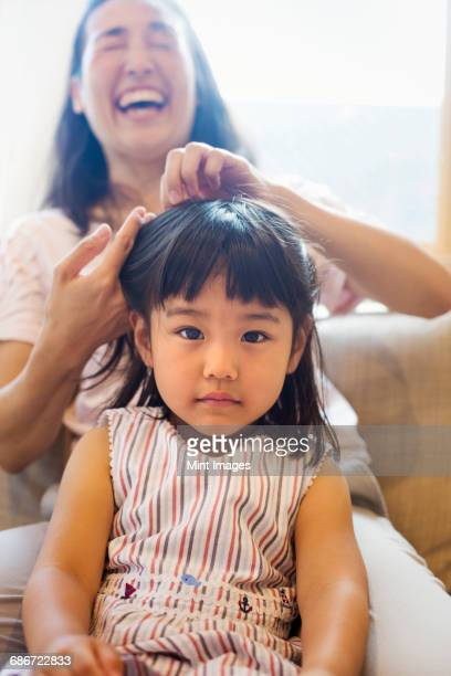 Family home. A mother combing her daughters hair.