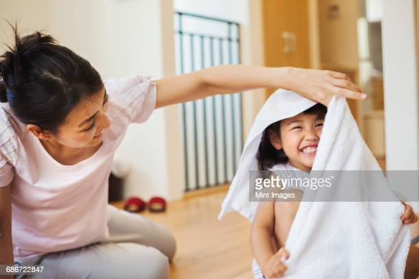 Family home. A woman and her daughter folding clean laundry.