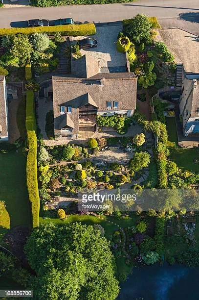 Family homes and green summer gardens aerial photo