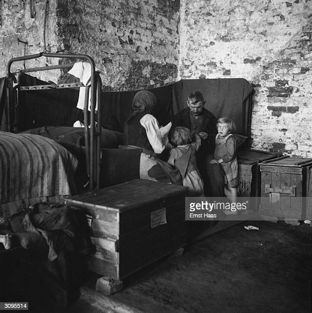 A family huddle together in a makeshift bedroom in postwar Vienna