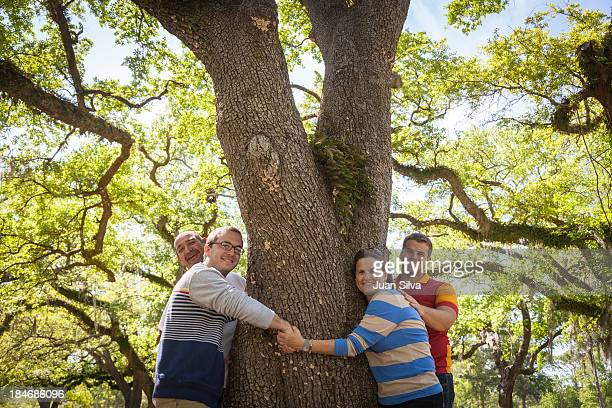Family hugging a tree trunk in the park