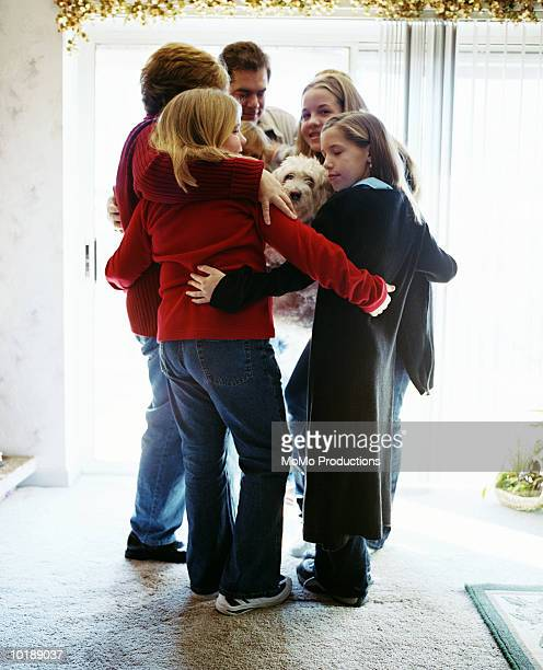 family hugging in living room - medium group of people stock pictures, royalty-free photos & images