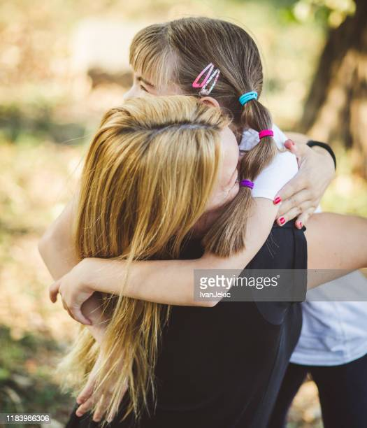 family hugging in the park - ivanjekic stock pictures, royalty-free photos & images