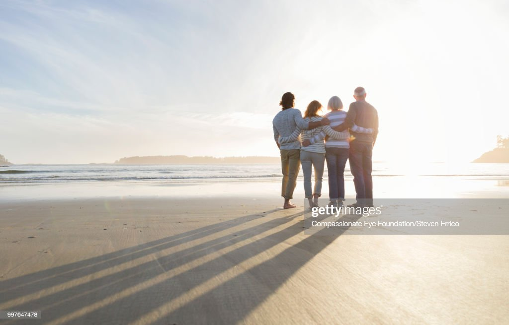 Family hugging on beach looking at ocean view at sunset : Stock Photo