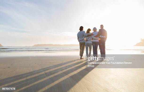 Family hugging on beach looking at ocean view at sunset