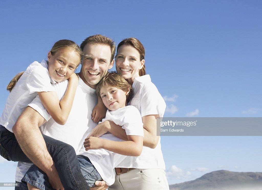 Family hugging outdoors : Bildbanksbilder