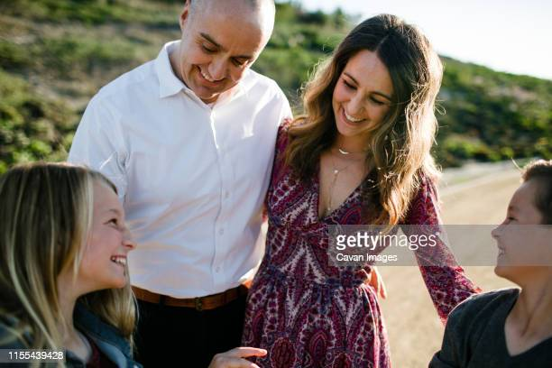 family hugs and smiling at one another in southern california - stepfamily stock photos and pictures