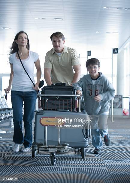 Family hurrying through airport with luggage cart