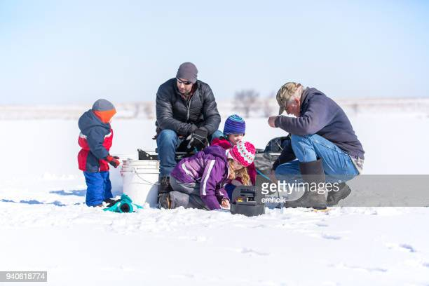 family ice fishing on late winter day - minnesota imagens e fotografias de stock