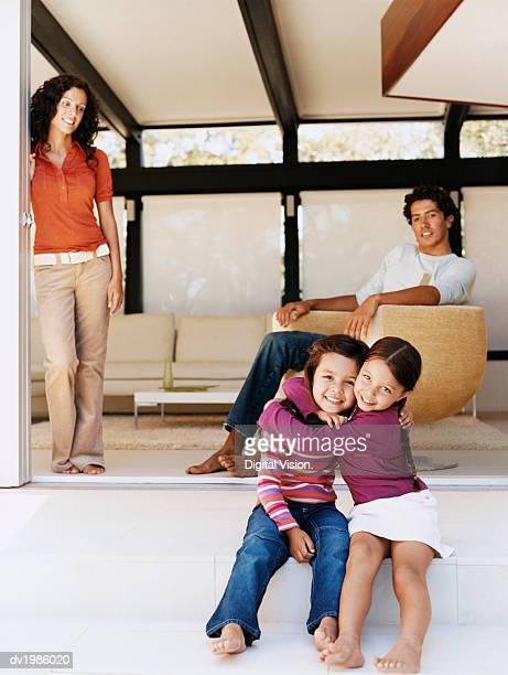 Family in a Living Room with Two Daughters Hugging