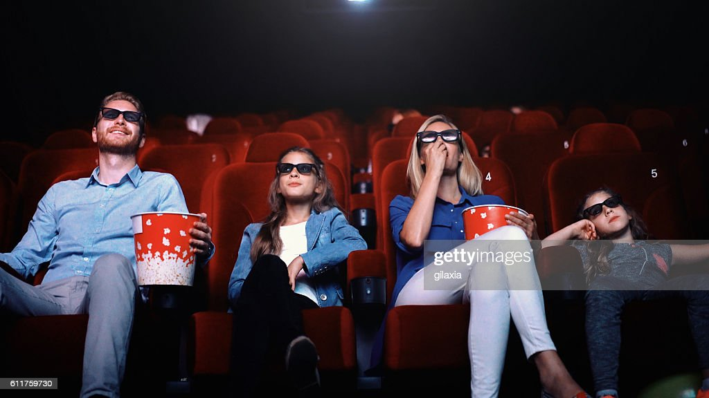 Family in a movie theater. : Stock Photo