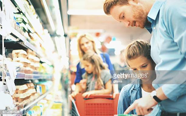 family in a supermarket. - convenience store stock photos and pictures