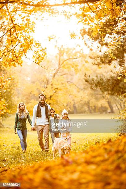Family in autumn park with their dog