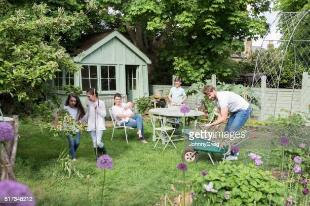 family in back garden, father gardening with wheelbarrow - shed stock pictures, royalty-free photos & images