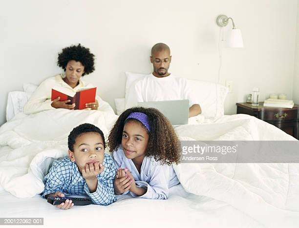 Family in bed, children (6-8) watching TV while parents read