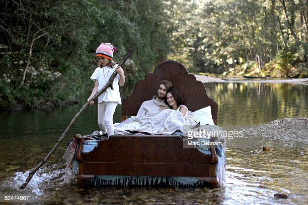 family in bed, in water, like a raft - naturist family stock photos and pictures