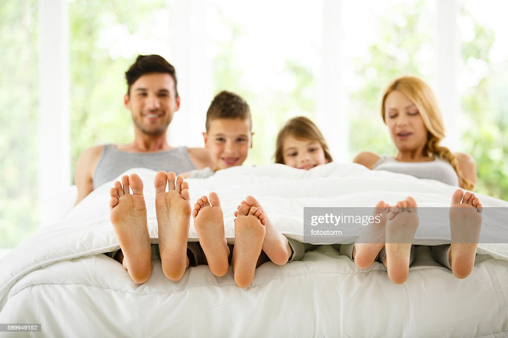 family in bed showing feet under duvet stock photo