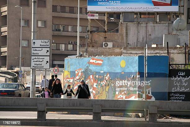 CONTENT] A family in Beirut Lebanon crosses the street in front of a patriotic mural