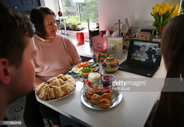 Family in Birkenhead, north west England speak to their mother and grandmother online via a laptop computer with an afternoon tea to celebrate...
