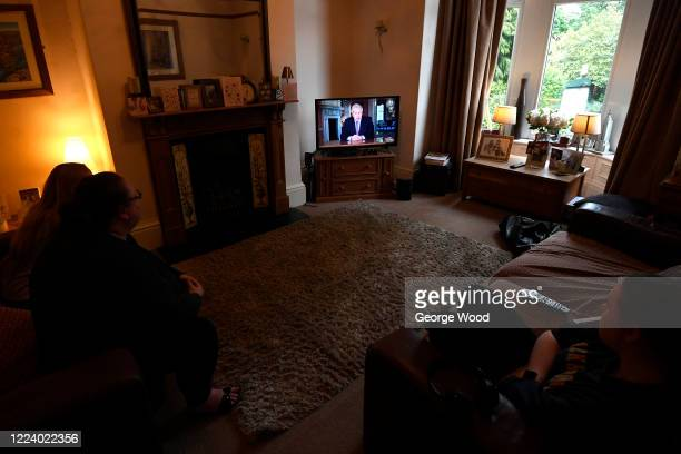 Family in Bradford watch Britain's Prime Minister Boris Johnson give a televised message to the nation to announce a new alert system and a possible...