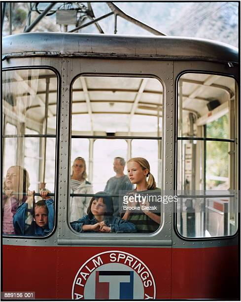 Family in cable car, children (6-14) looking out of window