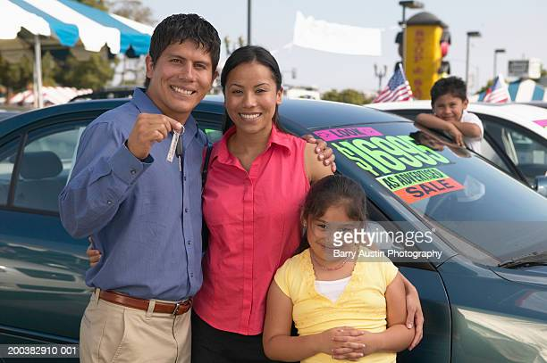Family in car lot, father holding keys, smiling, portrait