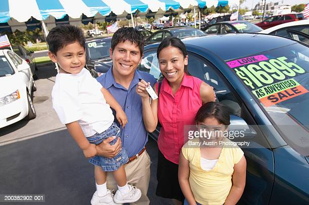 Family in car lot, mother holding keys, smiling, portrait