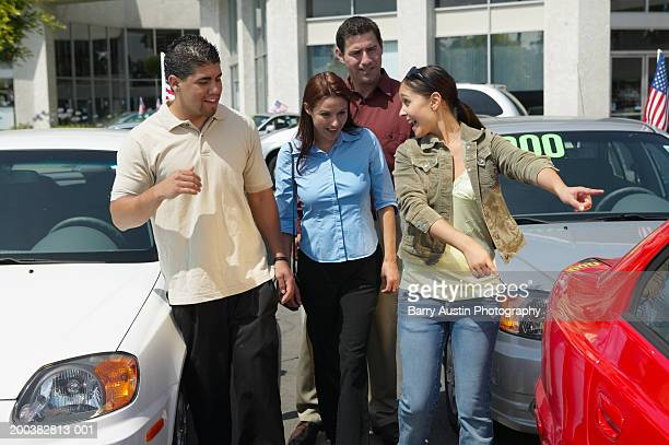 family in car lot, teenage girl (17-19) pointing at car, smiling - four people in car stock pictures, royalty-free photos & images