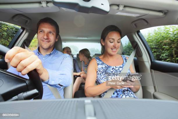 family in car, mum looking at phone - family driving stock photos and pictures