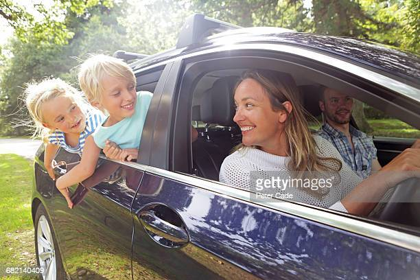 family in car on country road - road trip stock pictures, royalty-free photos & images