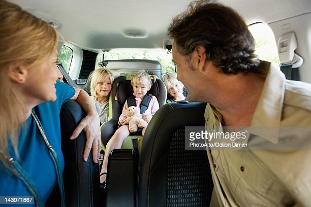 Family in car, parents looking over their shoulders at children