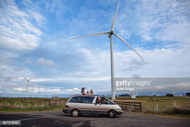 family in car parked beneath a large wind turbine