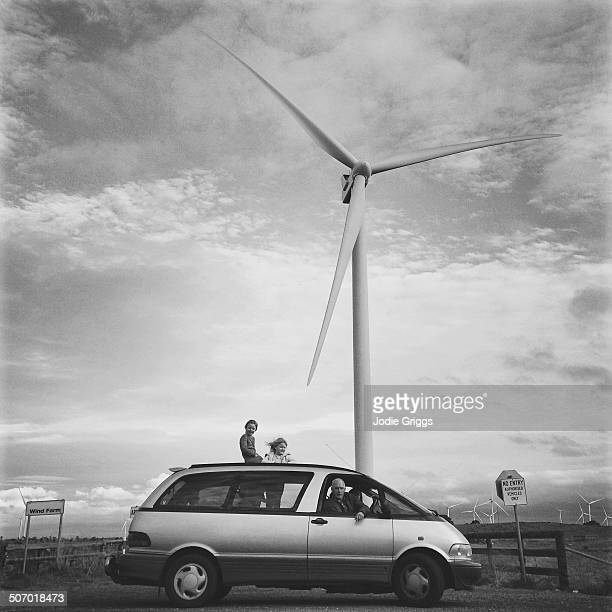 Family in car parked beneath large wind turbine