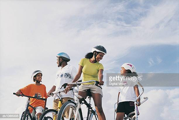 Family in Cycle Helmets on Bicycles